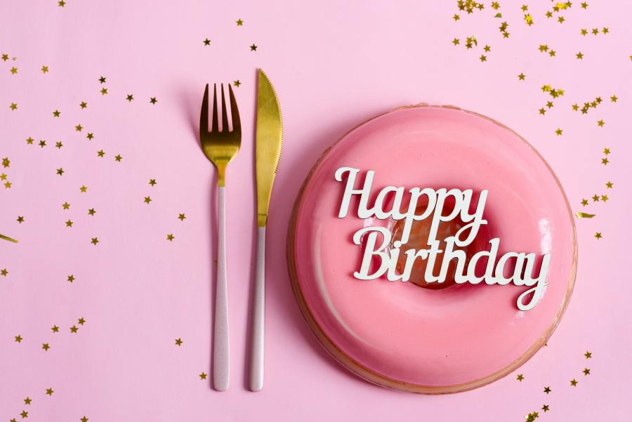 text happy birthday above freshly cooked homemade fruit glazed dessert on a pink background with