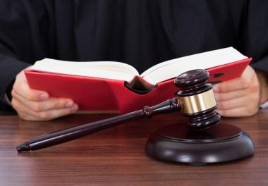 Dommer med lovbok og klubbe