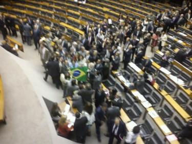 Deputados comemoram e cantam o hino nacional com a bandeira brasileira. Foto de Thiago Skárnio sob licença CC