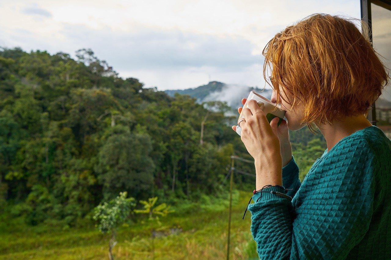 mujer bebiendo café en la ventana