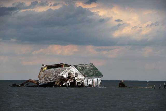 The last house on Holland Island in Chesapeake Bay, which once had a population of almost 400,  finally toppled in October 2010. As the water rose and the island eroded, it had to be abandoned. Astrid Riecken for The Washington Post, via Getty Images