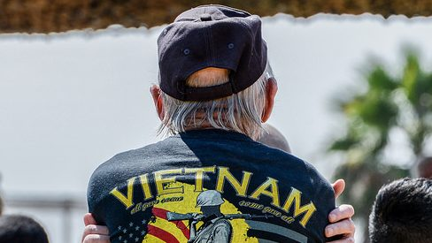 """Vietnam Veteran stands with his back to the came; jacket reads, """"Vietnam"""" across the back"""