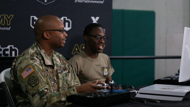Two Soldiers play video games in front of a background that says Army Entertainment and Twitch.