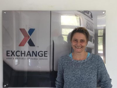 Heike Molter stands in front of a glass wall with the Exchange logo in the background