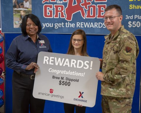 Leatrice Peyton, Shaw Exchange store manager, and Col. Richard Brown, 20th MSG Commander, present Bree Dippold with her $500 gift card