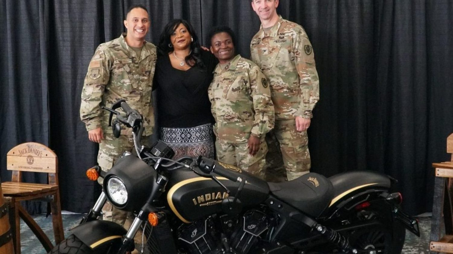 Three Soldiers in uniform stand with an Army veteran behind an Indian motorcycle