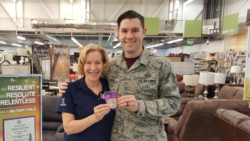 During the Month of the Military Child, RAF Mildenhall Exchange's Susan Kolbe presents a Military Brat patch to her son, Jonathan. Jonathan is stationed 10 miles away at RAF Lakenheath. Both installations are in the United Kingdom.