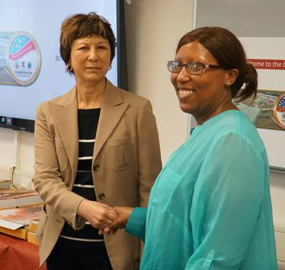 Executive Vice President and Chief Logistics Officer Karen Stack presents a coin to FA Manager Dwana Harper. Harper, who has worked with the Exchange for 10 years, helped the European commissaries transition smoothly to the new warehouse ordering system at the Germersheim DC.