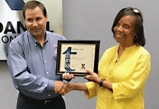Dan Daniel DC manager Sarah Lee receives her 30-year service award from Alan French, vice president of the Logistics Directorate. French's dad hired Lee to work at the DC.