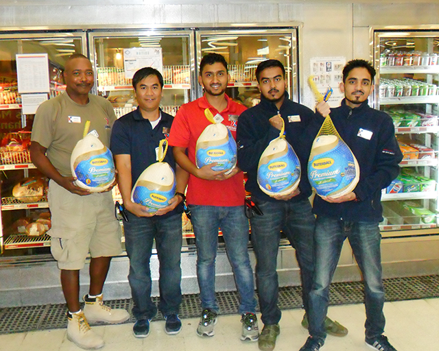 Exchange associates help load turkeys into the freezer at the Qatar's Al Udeid AB Exchange.  From left: Store Manager Dennis Dawson and associates Jofre Palinlin, Prakash Rijal,  Kutub Uddin and Prem Khadka.