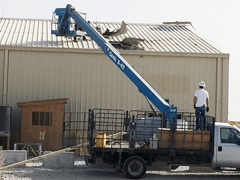 Workmen repair the roof of Bagram AB's Warrior Exchange in Afghanistan after the building took a direct hit from a rocket.