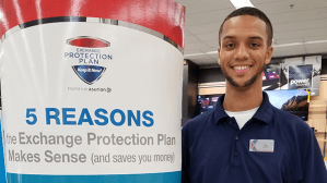 Associate beside an Exchange Protection Plan promotional sign.