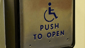 A push to open door sign showing a wheelchair icon.