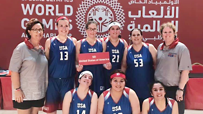 Fort Sam Houston Associate Jamie Holt, holding sign, joins her teammates at the Special Olympics World Games.
