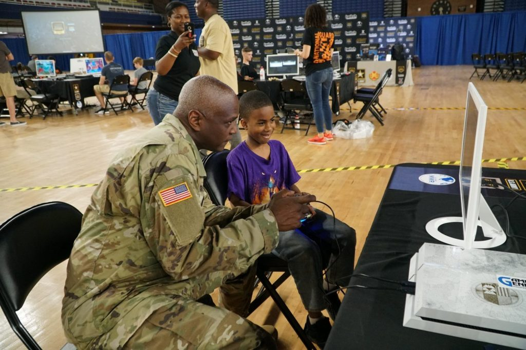 A Soldier plays a video game with a child; a woman in the background is taking a photo with her phone