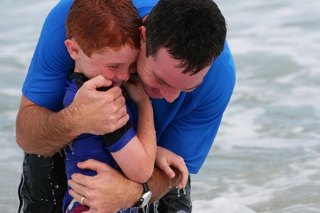 Rodney Gage, pastor of Fellowship of Orlando church, baptizes his son, Luke, who was one of 34 people baptized at the church's July 22 Celebration of Baptism at Cocoa Beach, Fla.  Photo courtesy of Fellowship of Orlando