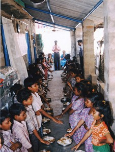 """Pastor Tata, the orphanage director, stands with teachers nearby, leading Indian children in prayer before a meal. """"They eat rice every meal,"""" Deb Corkern, co-founder of the orphanage, said. """"Sometimes they get vegetables with the rice. On special occasions they add chicken."""""""