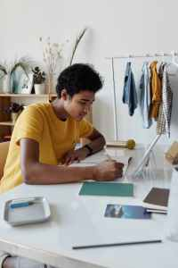 boy wearing yellow shirt while writing on white paper