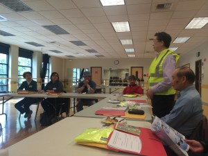 Alan Lai demonstrates safety vest use at a training for apartment managers. Trainees received the vests and emergency signage to post in their buildings.