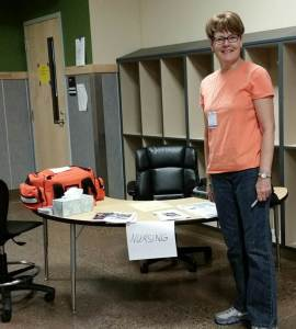 King County Public Health Reserve Corps nurse Becky Huwe sets up the medical area at Coulee Dam shelter.