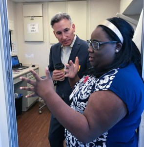 Executive Dow Constantine hears from a provider during a school-based health center tour at Highland Middle School