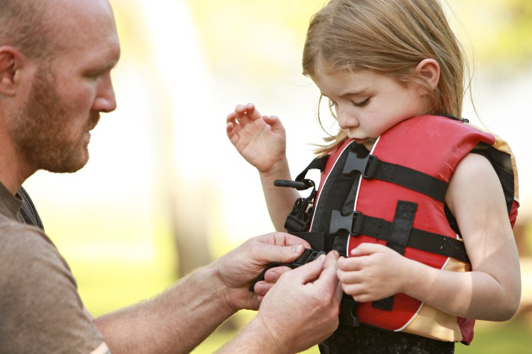 dad putting life jacket on girl