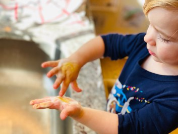 Boy washes paint off of hands.