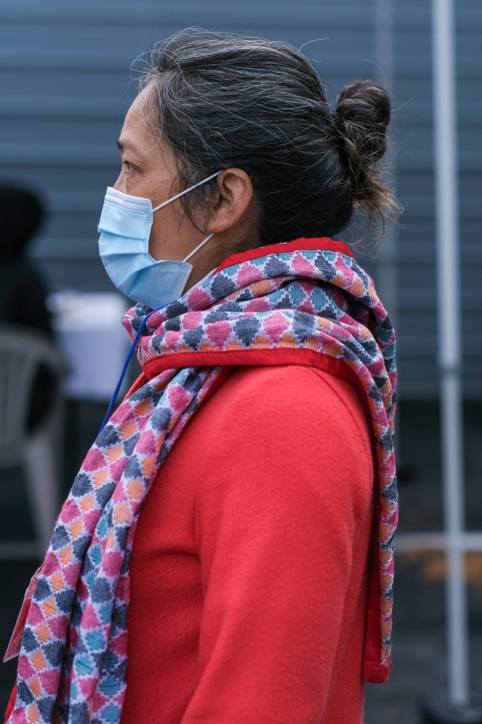 Woman in blue surgical mask, red sweater and brightly colored scarf