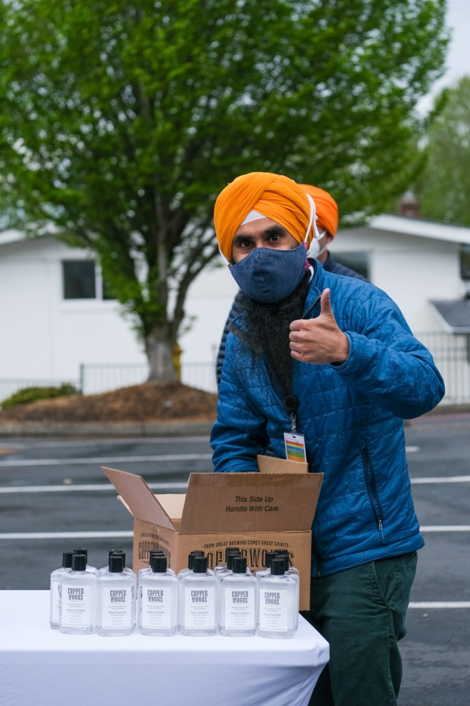 Man with blue mask and orange turban gives a thumbs up sign