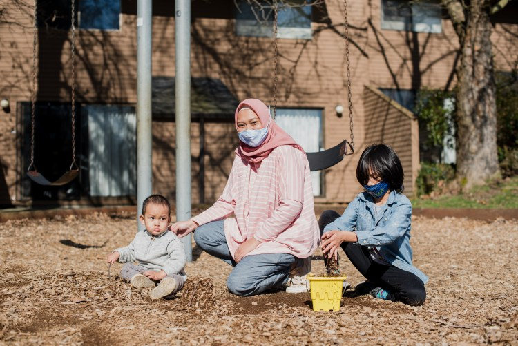A woman in a pink hijab and mask poses at a playground with a baby and young child.