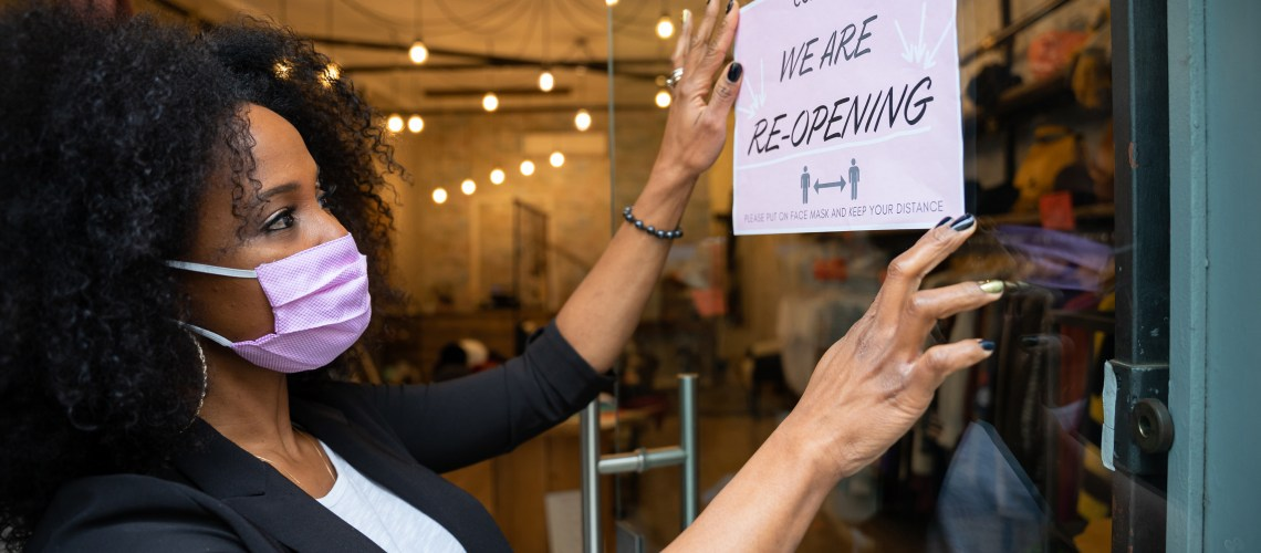 """Black woman wearing a mask, putting up a sign in a shop window that reads """"We are reopening"""""""