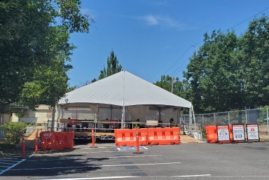 White canvas tent canopy which serves as the Angle Lake COVID-19 testing site in the city of SeaTac. Orange and white signage out front.