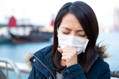 Woman wearing face mask with hand to mouth and coughing