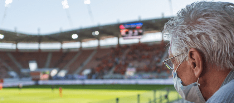 Close up image of a man with gray hair, glasses, and a mask in the stadium for a large sports game.