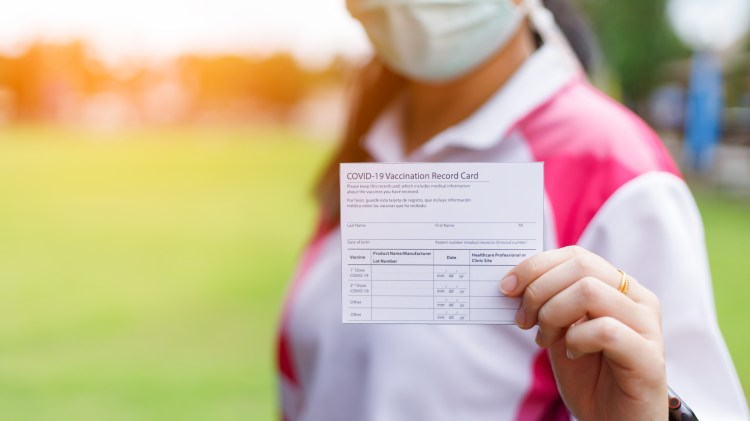 Close up of a woman holding up a COVID-19 Vaccination Record card. The person is masked and standing outside.
