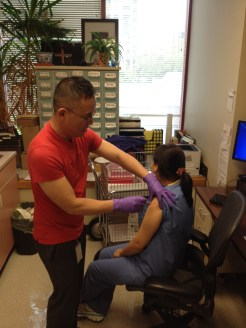 Tai Huynh, RN, of Downtown's flu clinic, gives a flu shot to Dental Assistant Thuy Chung.