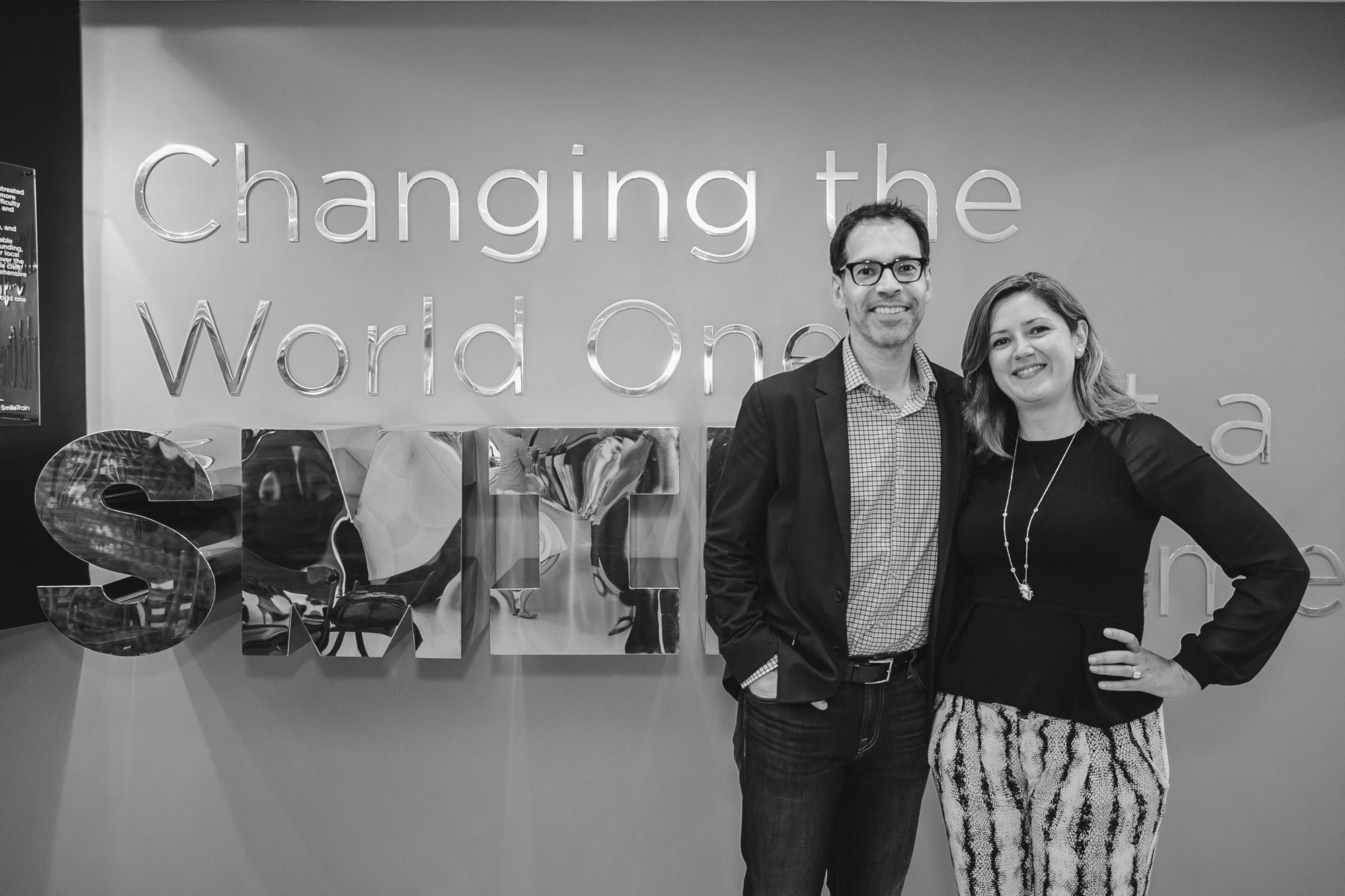 Two people standing in front of sign saying 'Changing the world one smile at a time'