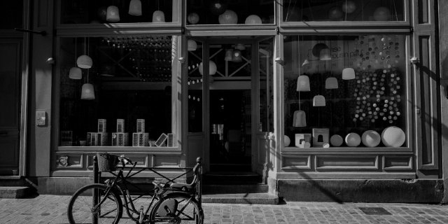 store front with hanging lamps and bicycle in front of it