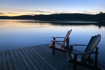 Muskoka chairs on a dock in front of a lake
