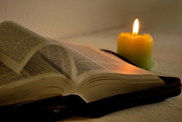 Open Bible with a candle