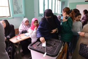 Woman casts her ballot in Egypt's 2014 constitutional referendum as child looks on © Bora S. Kamel | Flickr