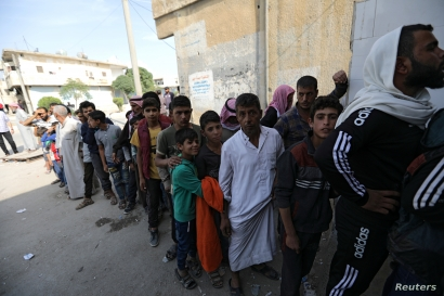 People stand in a queue to receive bread in the border town of Tal Abyad, Syria, Oct. 18, 2019.