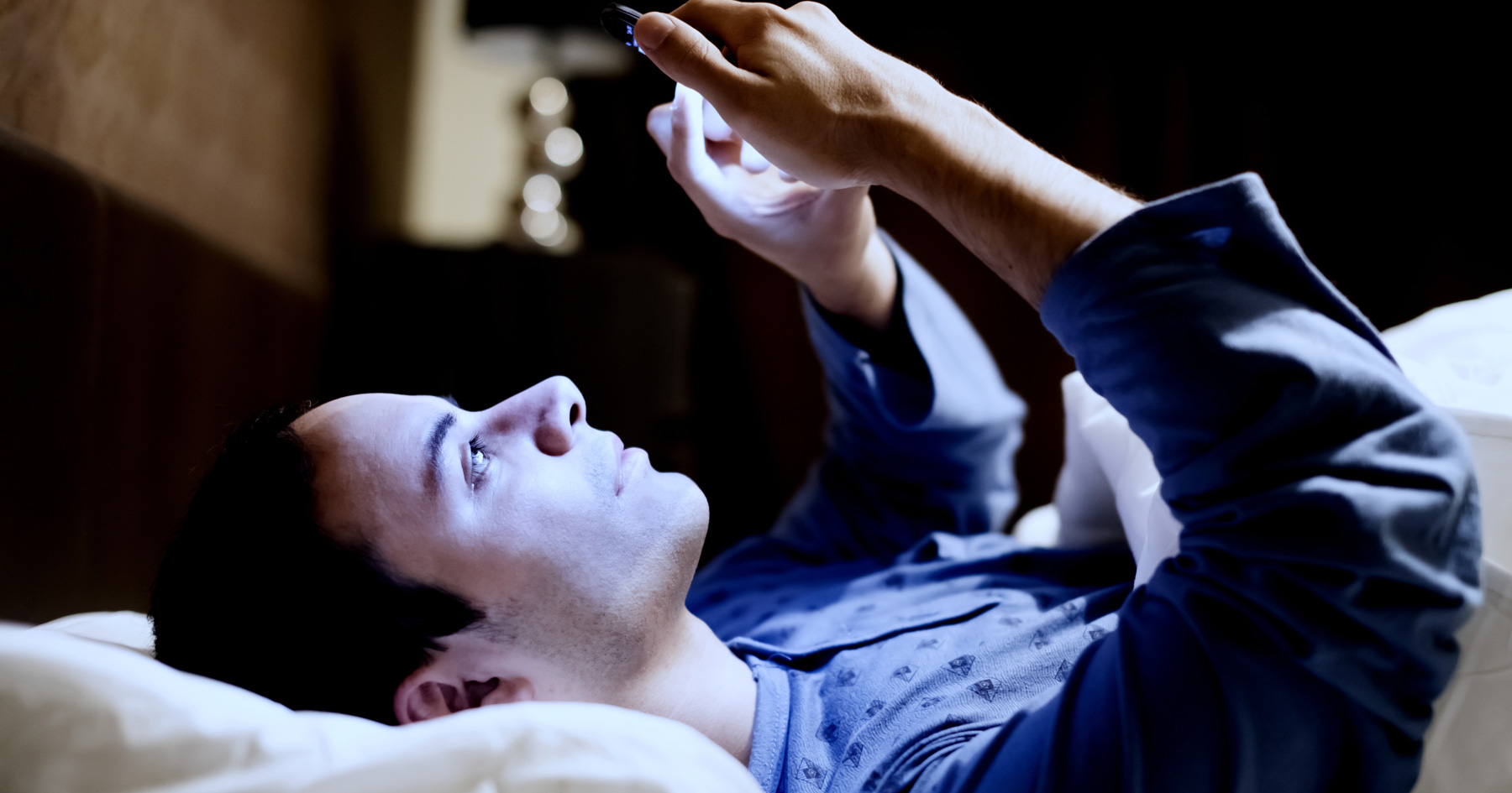 Picture of a guy using his phone before he goes to sleep