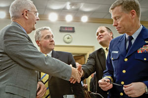 Bresland (from left), Buckner, Bayer Vice President Nick Crosby, and U.S. Coast Guard Rear Adm. James Watson converse after the hearing.