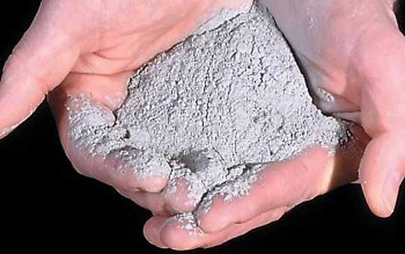 Close-up photograph of person's hands holding half a cup of rock flour