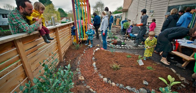 Various small children and adults work together to build a school garden