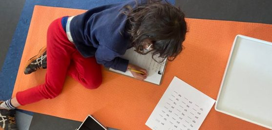 A 3rd grade child stretches out on a brightly colored floor mat while doing math problems on paper