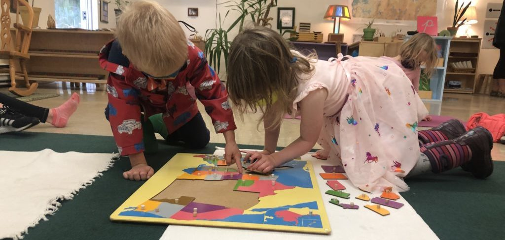Two four year olds work on a colorful USA map puzzle together