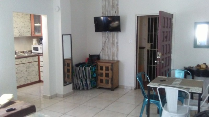 View of living/dining area, kitchen and front door (open with gate). Note, apartment now unfurnished