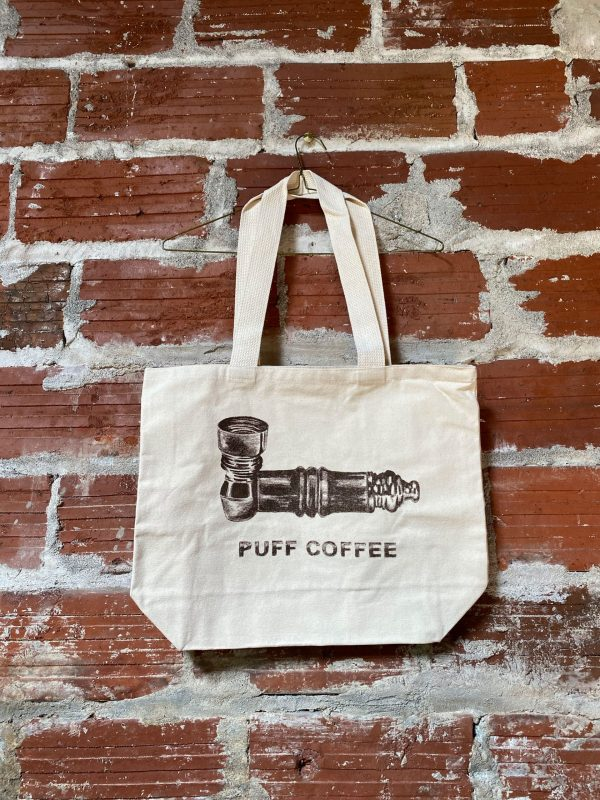 white puff coffee tote against a brick wall